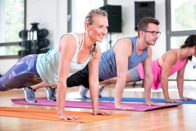 Il bello gruppo dell'uomo delle donne sta facendo l'allenamento di forma fisica di sport in una palestra fotografia stock