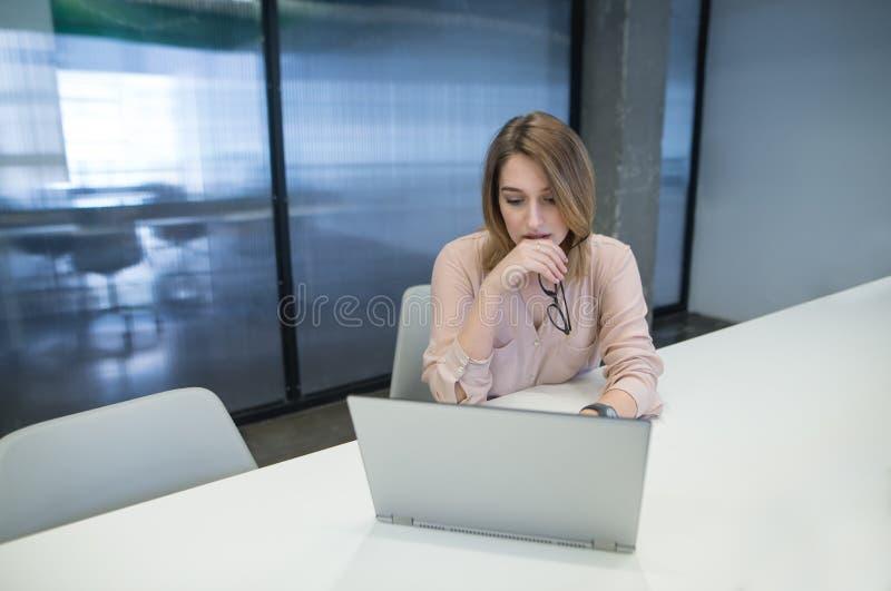 il bello impiegato di concetto sta esaminando il computer l'estremità Bella ragazza che lavora ad un computer portatile nell'uffi fotografie stock libere da diritti