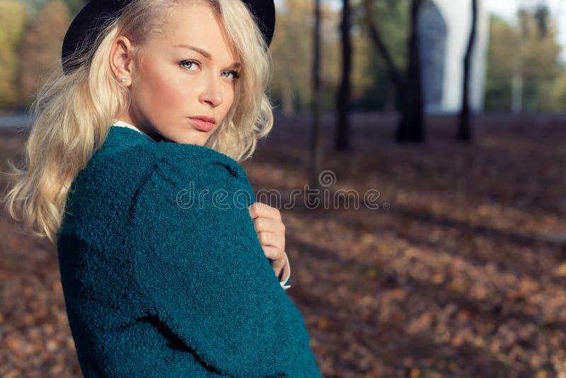 Il bello innamorato sexy una ragazza felice la bionda in un rivestimento ed in un cappello caldi cammina nel parco della città ne fotografie stock