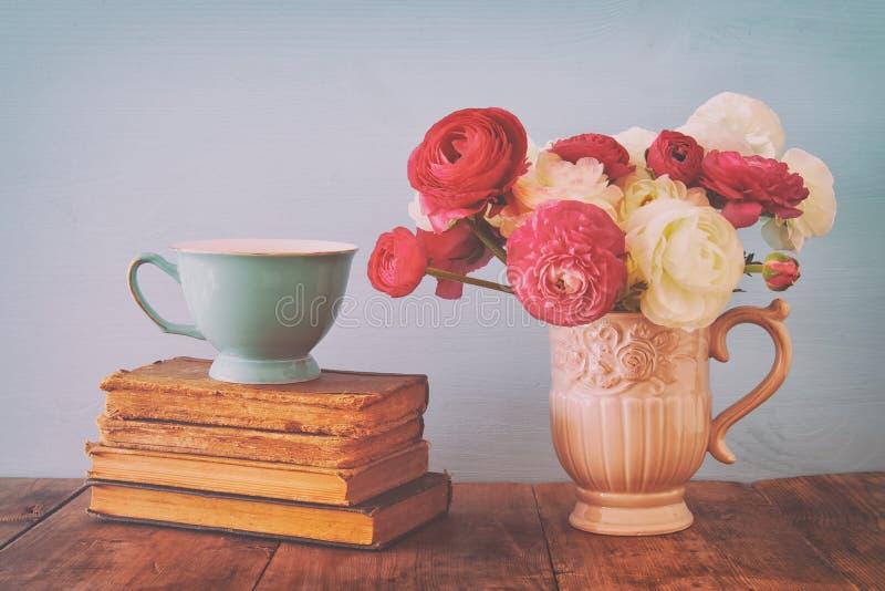 Il bello mazzo della molla fiorisce nel vaso accanto ai vecchi libri sulla tavola di legno immagine stock libera da diritti