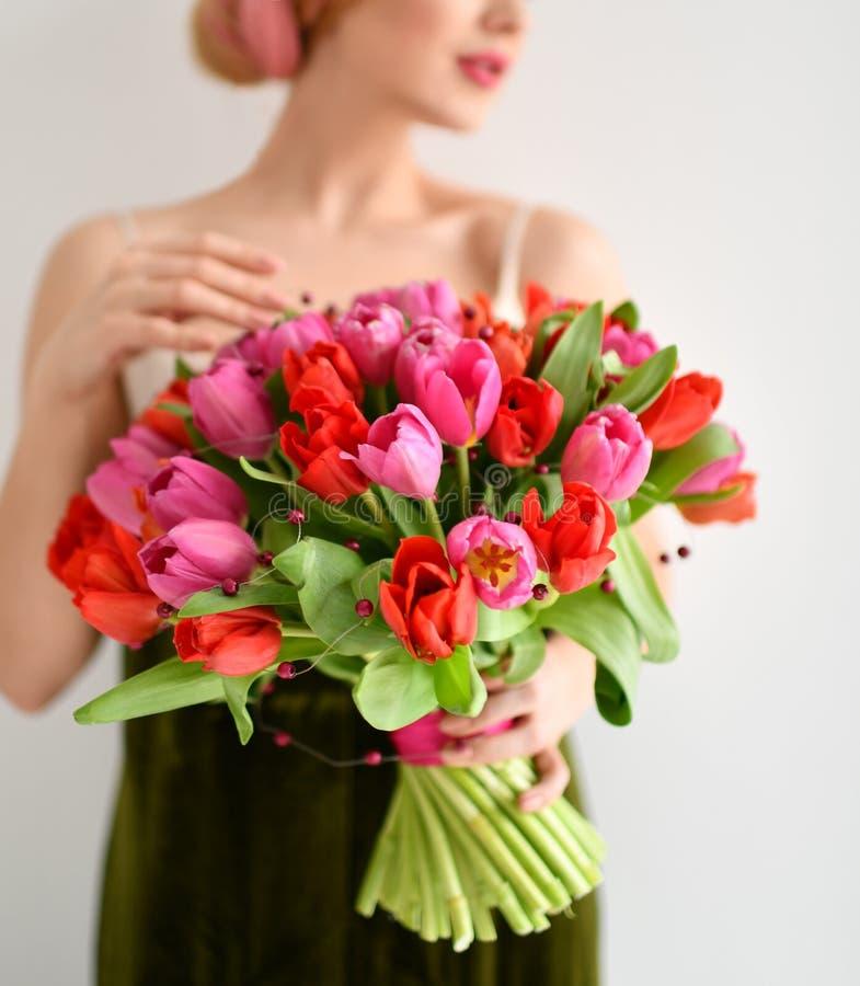 Il bello mazzo della tenuta della donna dei tulipani di rossi carmini fiorisce su grey fotografia stock libera da diritti