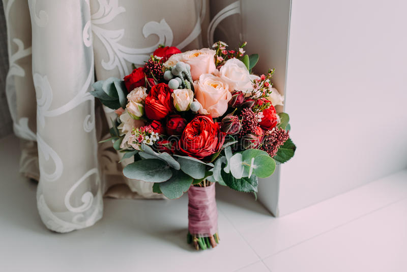 Il bello mazzo di nozze dei fiori rossi, i fiori rosa e la pianta stanno accanto alla finestra fotografia stock