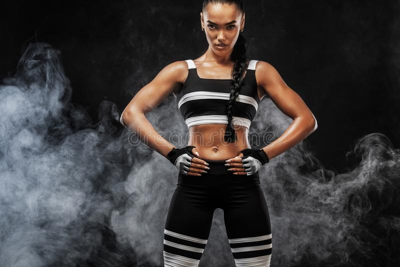Il bello modello afroamericano sportivo, donna in sportwear fa la forma fisica che si esercita al fondo nero per restare adatto immagine stock