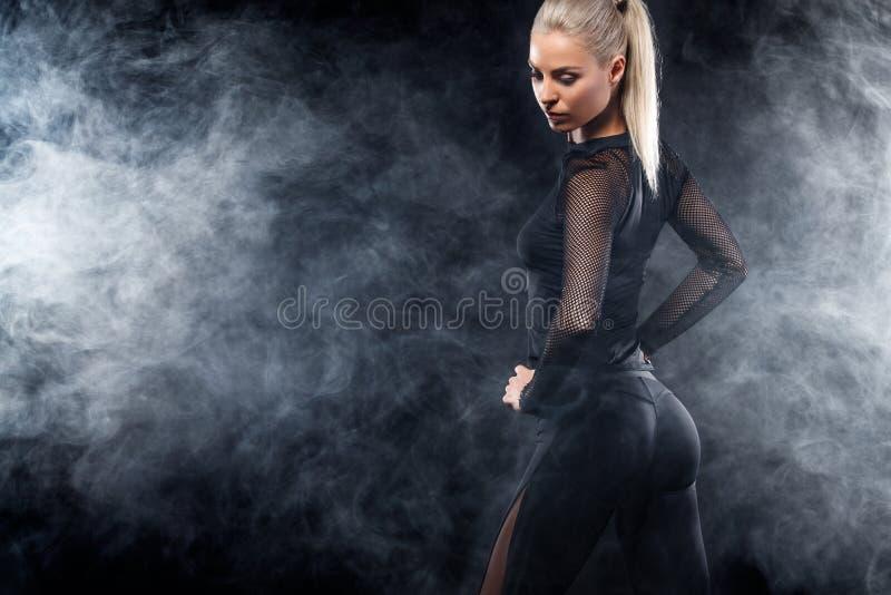 Il bello modello afroamericano sportivo, donna in sportwear fa la forma fisica che si esercita al fondo nero per restare adatto fotografie stock
