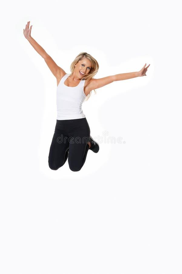Il bello modello biondo in attrezzatura della palestra salta per la gioia, isolato sopra fotografia stock libera da diritti