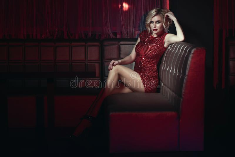 Il bello modello con provocatorio compone il vestito misura breve rosso d'uso dallo zecchino che si rilassa sul sofà quadrato in  fotografia stock