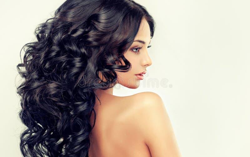 Il bello modello della ragazza con il nero lungo ha arricciato i capelli fotografia stock