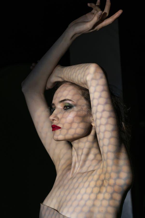 Il bello modello della ragazza con le labbra rosse compone e spalle nude coperte di maschera sotto forma di rete di esagonale immagini stock libere da diritti