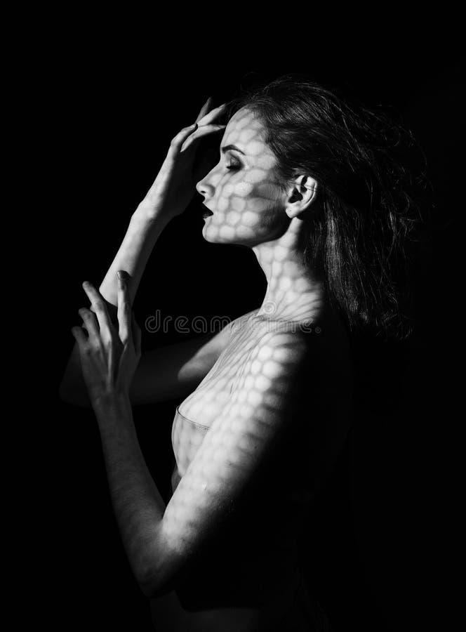 Il bello modello della ragazza con le labbra rosse compone e spalle nude coperte di maschera sotto forma di rete di esagonale fotografia stock