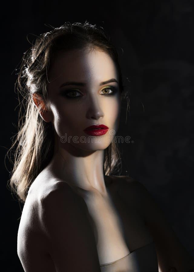 Il bello modello della ragazza con le labbra rosse compone e spalle nude nella tonalità, con una siluetta accesa e una striscia d immagini stock libere da diritti