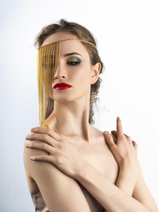 Il bello modello della ragazza con le labbra rosse prepara e spalle nude che indossano i gioielli concettuali di modo fatti delle fotografia stock