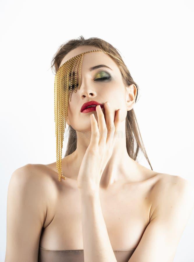 Il bello modello della ragazza con le labbra rosse prepara e spalle nude che indossano i gioielli concettuali di modo fatti delle fotografia stock libera da diritti