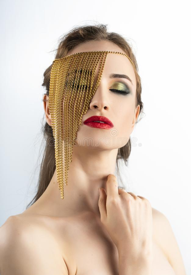 Il bello modello della ragazza con le labbra rosse prepara e spalle nude che indossano i gioielli concettuali di modo fatti delle immagine stock