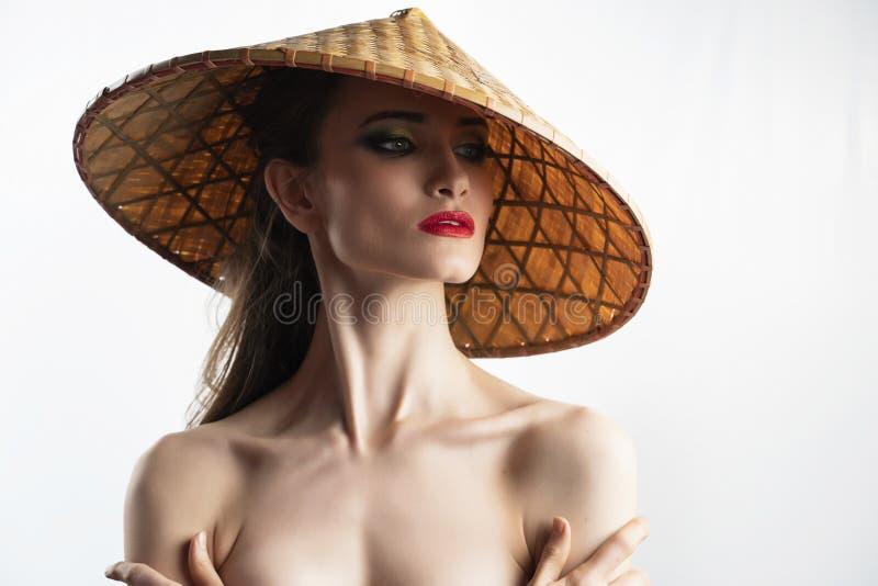 Il bello modello della ragazza con le labbra rosse prepara e spalle nude che portano il cappello vietnamita asiatico del cono fat fotografia stock libera da diritti