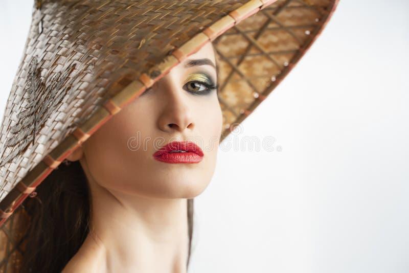 Il bello modello della ragazza con le labbra rosse prepara e spalle nude che portano il cappello vietnamita asiatico del cono fat immagini stock