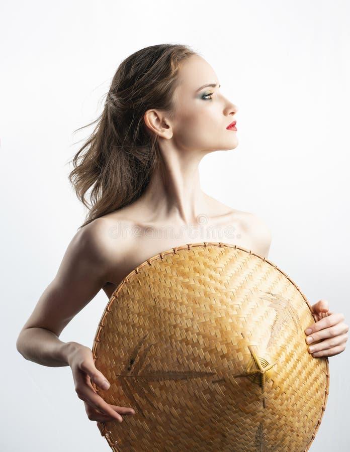 Il bello modello della ragazza con le labbra rosse prepara e le spalle nude guarda lateralmente e copre il suo seno di cappello v fotografie stock