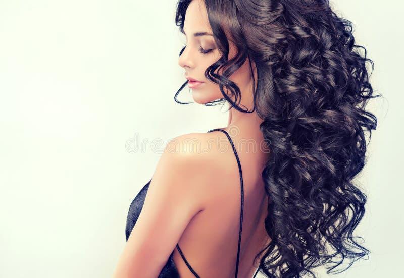 Il bello modello della ragazza del ritratto con il nero lungo ha arricciato i capelli fotografie stock libere da diritti