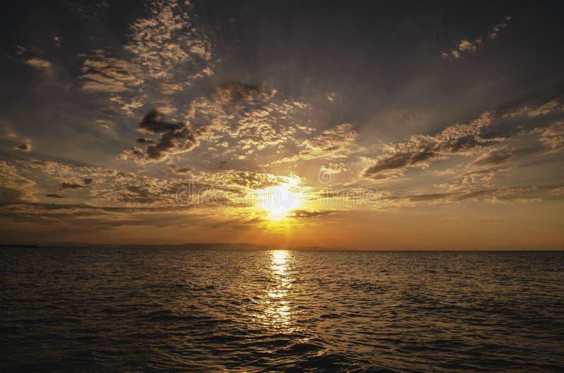 Il bello paesaggio ardente del tramonto in mare il mar Caspio ed il cielo arancio sopra con la riflessione dorata del sole impres fotografia stock