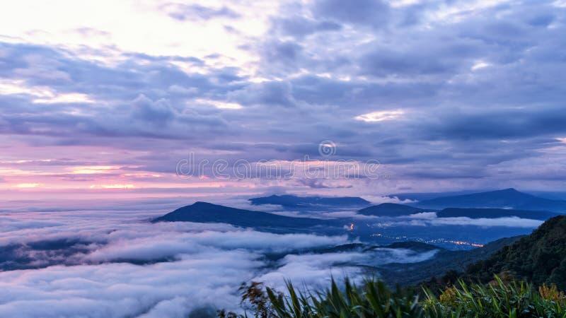 Il bello paesaggio della natura della nebbia copre la sommità ed il cielo variopinto durante l'alba nell'inverno, vista dell'ango immagini stock libere da diritti