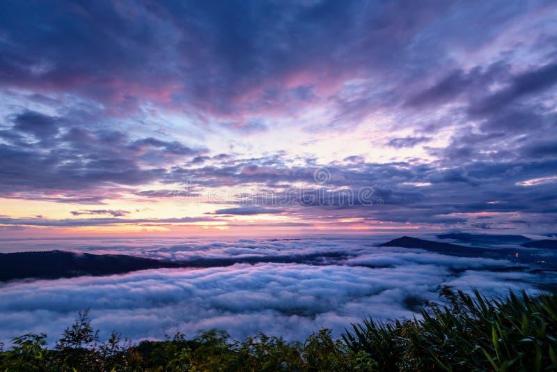 Il bello paesaggio della natura della nebbia copre la sommità ed il cielo variopinto durante l'alba nell'inverno, vista dell'ango fotografie stock