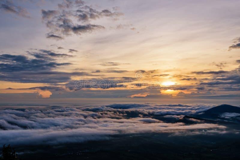 Il bello paesaggio della natura il sole è sopra la nebbia del mare a cui copre le montagne ed il cielo luminoso durante l'alba ne fotografie stock libere da diritti