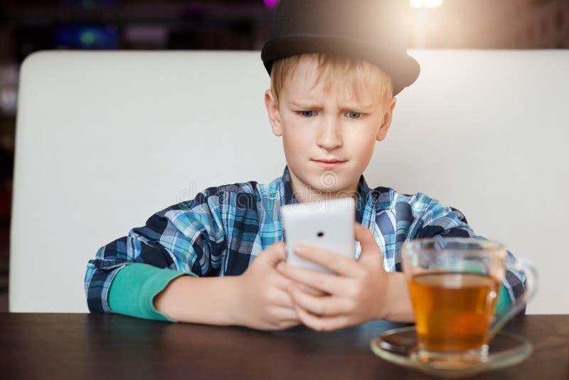 Il bello ragazzino alla moda si è vestito in ubicazione del berretto nero e della camicia controllata a messaggio di legno della  fotografie stock libere da diritti
