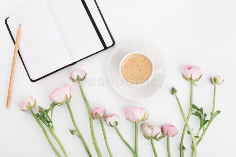 Il bello ranunculus della molla fiorisce, taccuino e tazza di caffè vuoti sulla tavola bianca da sopra Cartolina d'auguri Disposi fotografia stock