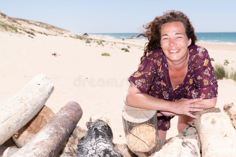Il bello ritratto del mezzo ha invecchiato la donna castana sulla spiaggia con legname galleggiante fotografia stock libera da diritti