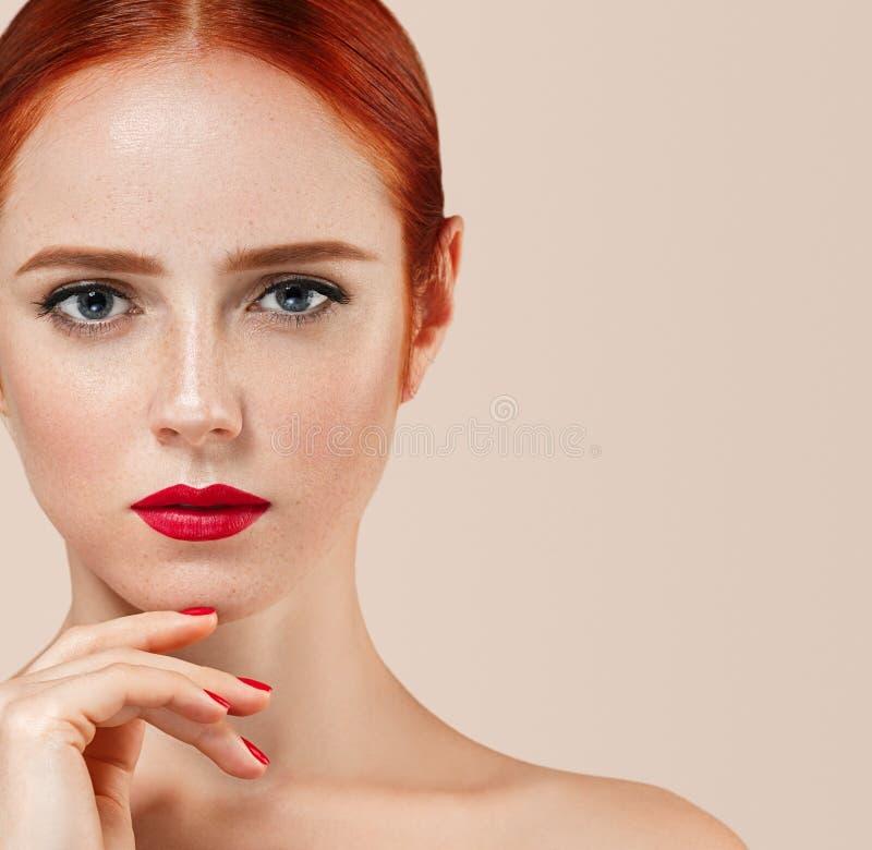 Il bello ritratto della donna con perfetto compone le labbra e le unghie rosse del manicure fotografia stock