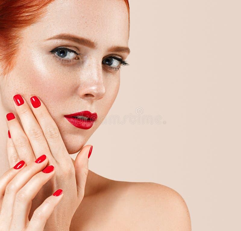 Il bello ritratto della donna con perfetto compone le labbra e le unghie rosse del manicure immagine stock libera da diritti