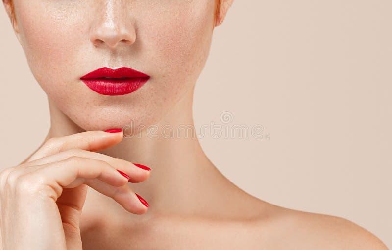 Il bello ritratto della donna con perfetto compone le labbra e le unghie rosse del manicure immagini stock
