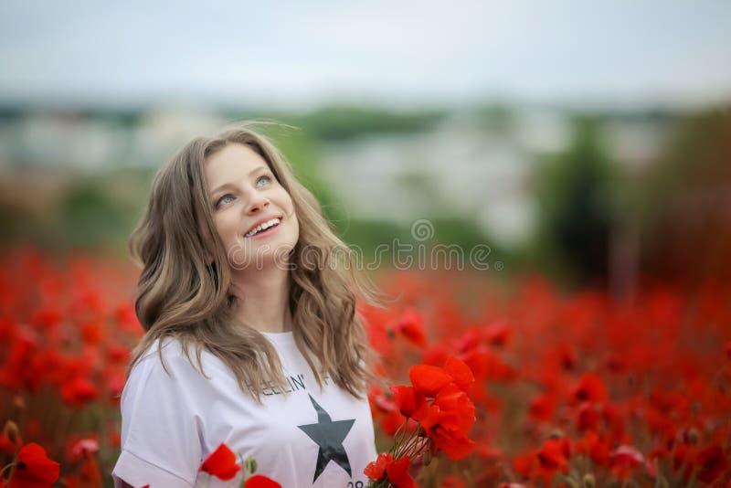 Il bello ritratto teenager sorridente felice della ragazza con i fiori rossi sulla testa che gode nei papaveri sistema il fondo d fotografia stock libera da diritti