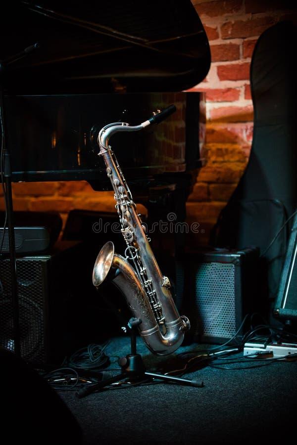 Il bello sassofono sta sul supporto in scena nella barra di jazz fotografie stock libere da diritti