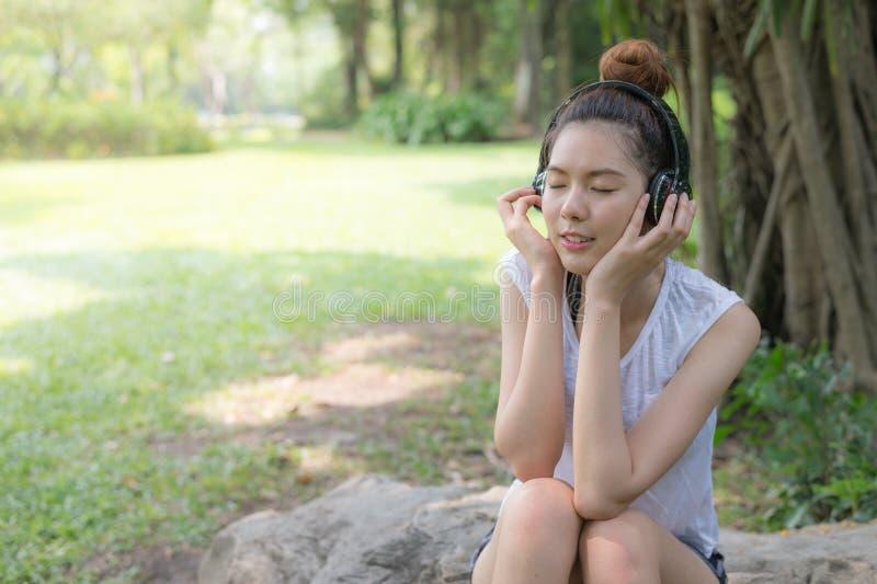 Il bello sorriso asiatico della donna e rilassarsi vicino ascoltano musica dalle cuffie stereo in giardino Con lo spazio della co immagini stock