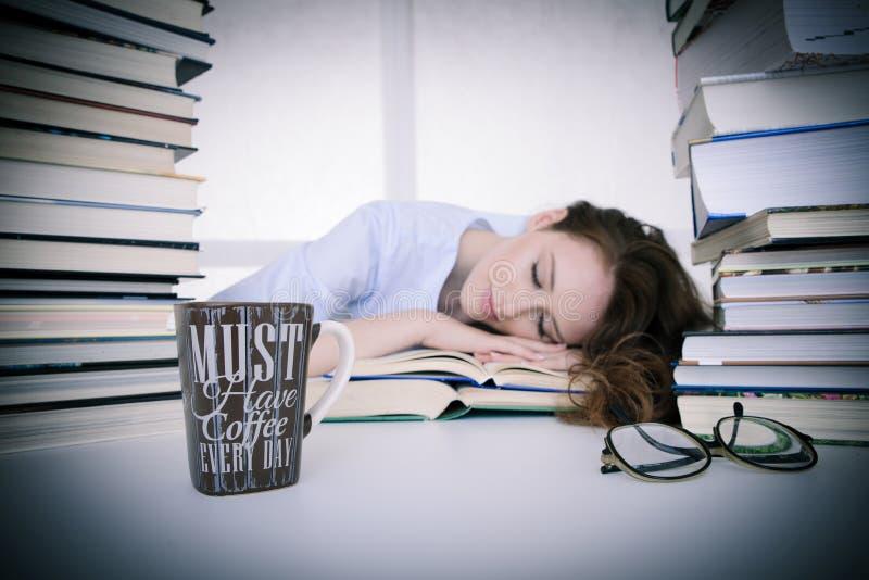 Il bello studente stanco attraente dorme sul mucchio dei libri con fotografie stock