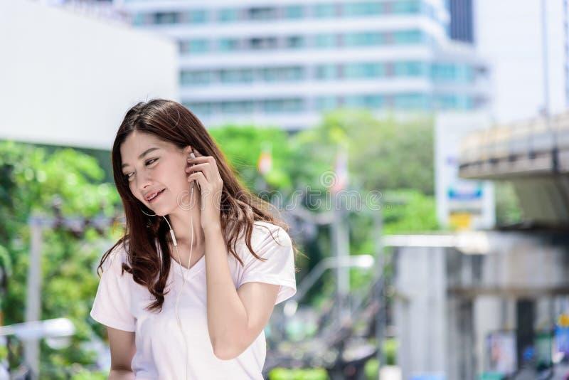 Il bello turista asiatico della donna ha musica che ascolta con la cuffia fotografia stock libera da diritti