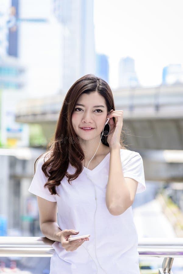 Il bello turista asiatico della donna ha musica che ascolta con la cuffia fotografie stock