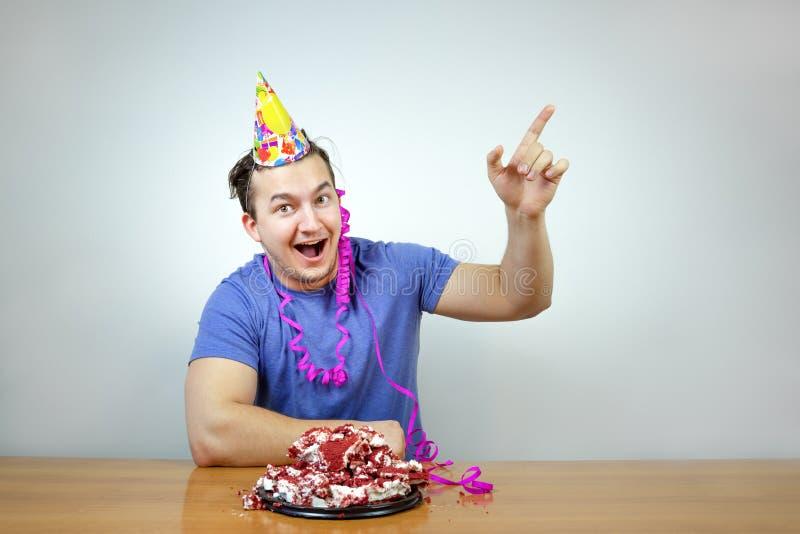 Il bello uomo caucasico emozionale con il cappello del cono della festa di compleanno sulla testa e sgualcisce il dolce alza il v fotografia stock