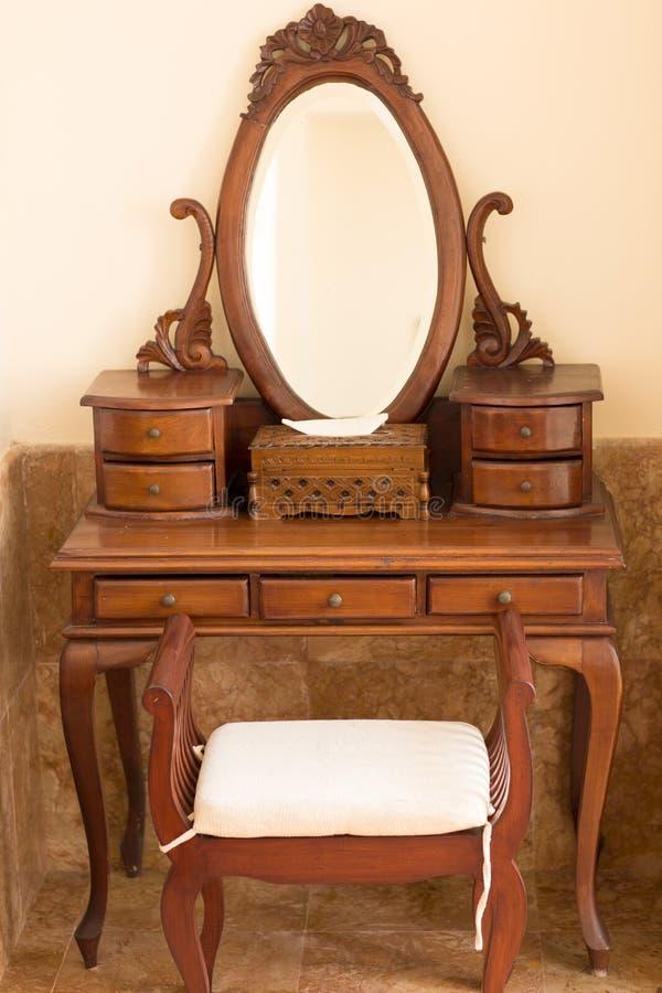 Il bello vecchio stile carwed la tavola di legno con lo specchio e la sedia immagine stock