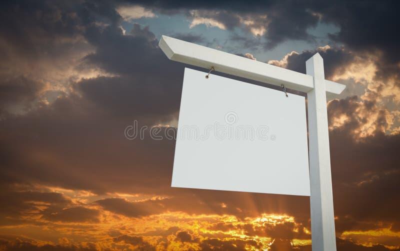 Il bene immobile bianco in bianco firma sopra il cielo di tramonto fotografia stock