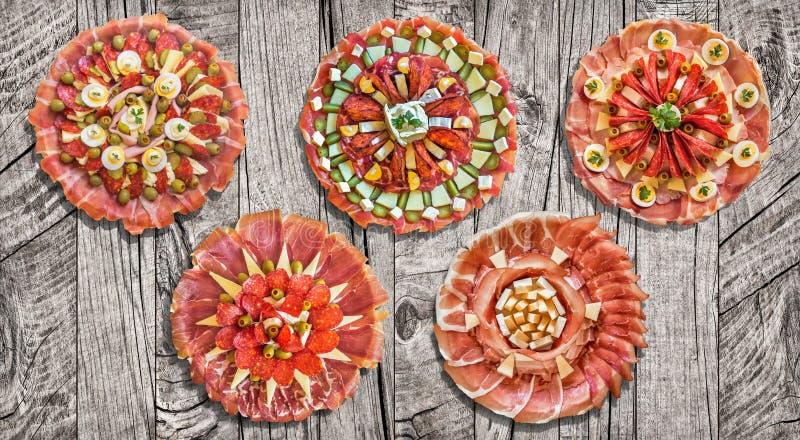 Il benvenuto tradizionale ha guarnito i piatti saporiti dell'aperitivo esibiti sulla vecchia superficie a fiocchi incrinata stagi immagine stock libera da diritti
