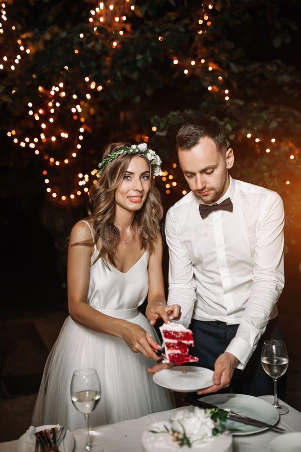 Il bianco e lo sposo dresed sposa hanno tagliato la torta nunziale sotto una La fotografia stock libera da diritti