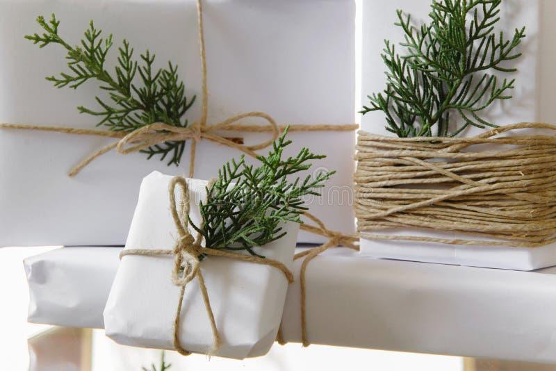 Il bianco elegante handcraft i contenitori di regalo ed i rami freschi dell'abete immagini stock