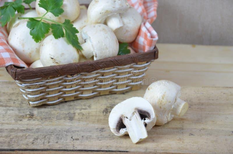 Il bianco fresco si espande rapidamente fungo prataiolo in canestro marrone su fondo di legno Vista superiore Copi lo spazio fotografia stock libera da diritti