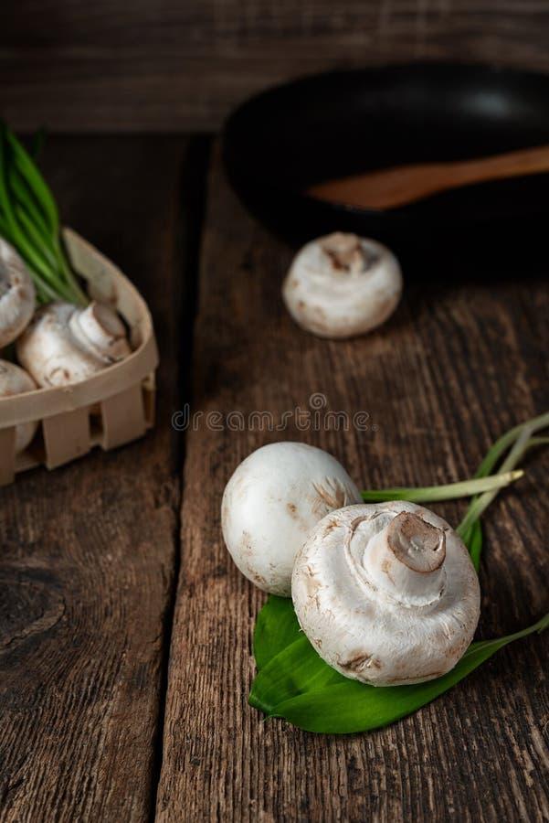 Il bianco fresco si espande rapidamente fungo prataiolo in ciotola marrone su fondo di legno Vista superiore fotografia stock libera da diritti