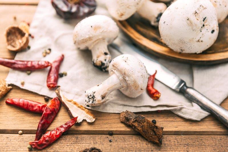 Il bianco fresco si espande rapidamente fungo prataiolo su fondo di legno fotografia stock