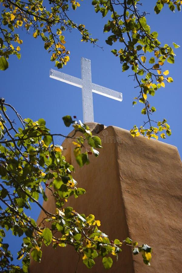 Il bianco ha acceso brillantemente l'incrocio di legno bianco contro la chiesa blu ricca dell'adobe di Santa Fe Mission dello skyo immagine stock