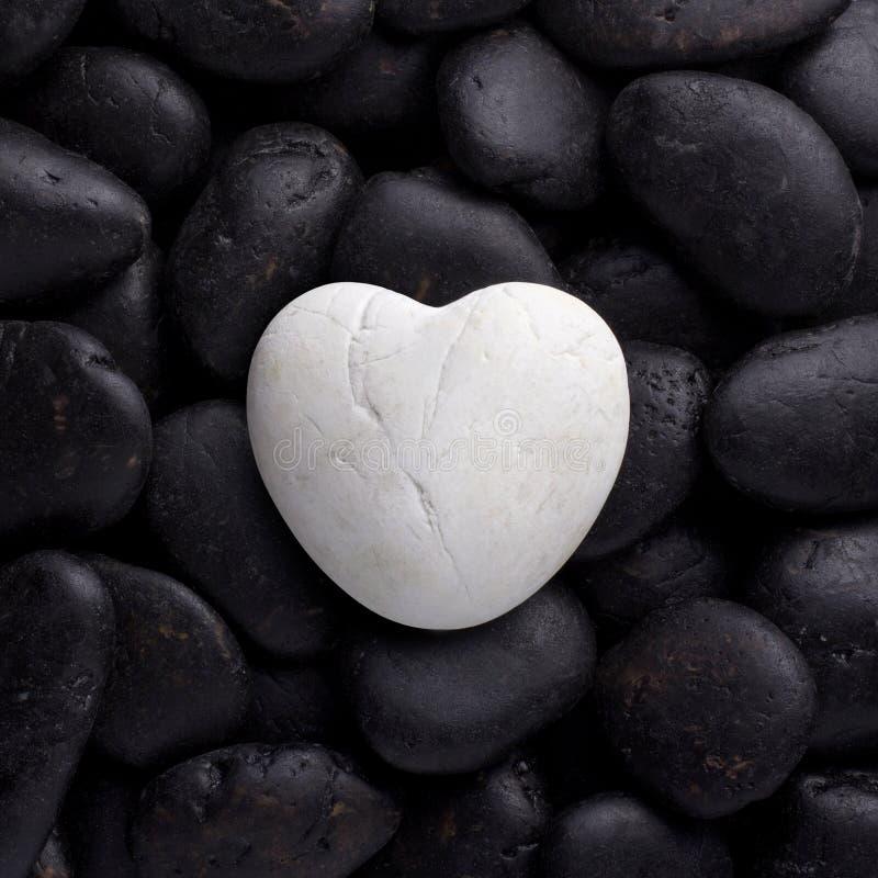 Roccia bianca, pietra nella forma del cuore sul ciottolo nero fotografie stock libere da diritti