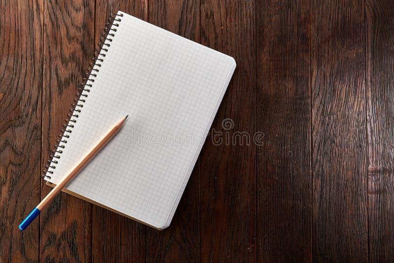 Il bianco ha controllato il quaderno con la matita sul bordo di legno di marrone del pino immagini stock