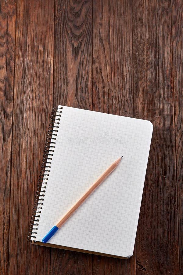 Il bianco ha controllato il quaderno con la matita sul bordo di legno di marrone del pino immagine stock